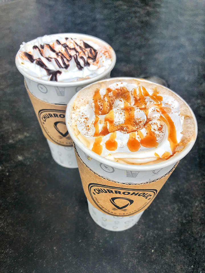Two hot coffees topped with drizzle